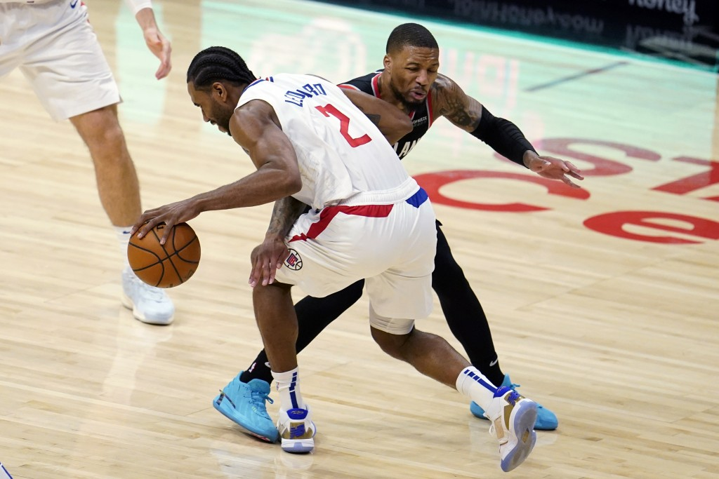 Los Angeles Clippers forward Kawhi Leonard (2) is defended by Portland Trail Blazers guard Damian Lillard during the first half of an NBA basketball g...