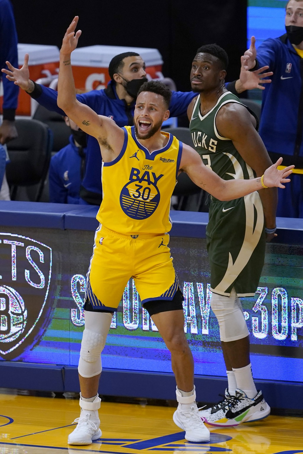 Golden State Warriors guard Stephen Curry (30) reacts after being fouled by Milwaukee Bucks forward Thanasis Antetokounmpo, rear, during the second ha...