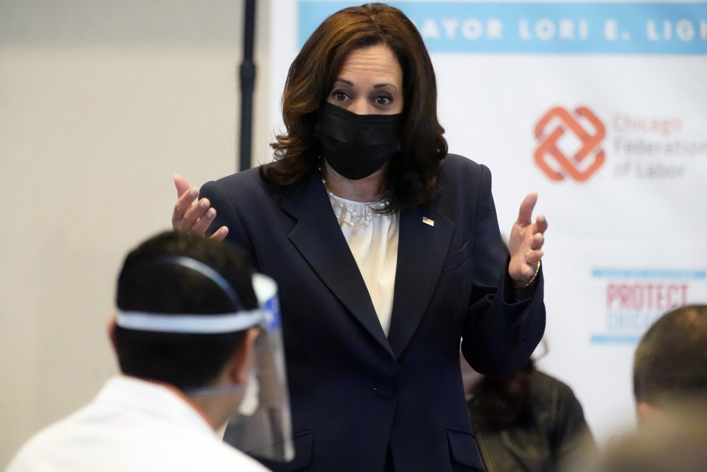 Vice President Kamala Harris looks at Osman Meah, a pharmacy manager at Jewel Osco who was giving the vaccinations, as she visits a COVID-19 vaccinati...