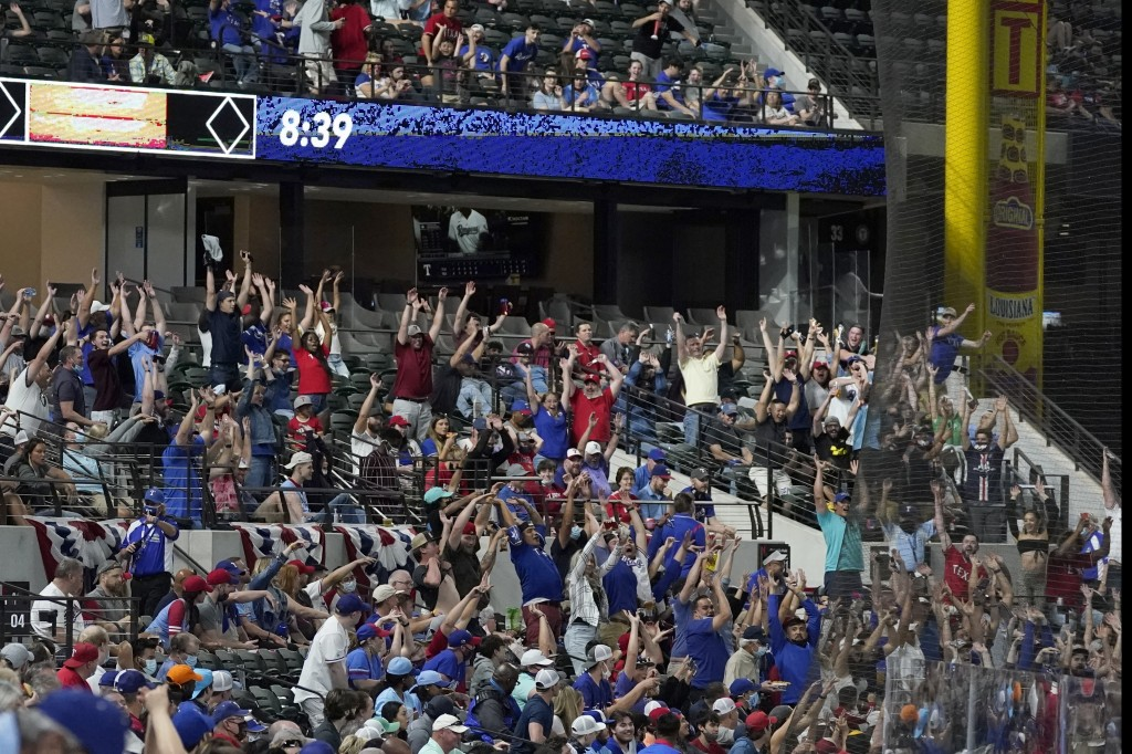 Fans participate in doing the wave as they watch the Toronto Blue Jays play the Texas Rangers in a baseball game in Arlington, Texas, Tuesday, April 6...
