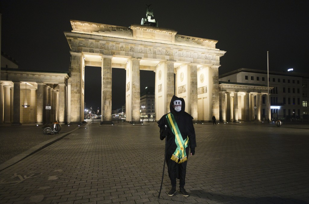 Brazilian activist and artist Rafael Puetter, dressed as the grim reaper, stands in front of the Brandenburg Gate during his one-man protest through B...