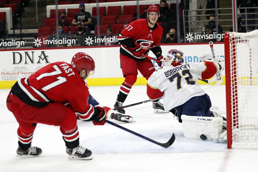 Carolina Hurricanes Andrei Svechnikov (37) and Jesper Fast (71) combine to challenge Florida Panthers goaltender Sergei Bobrovsky (72) during the seco...