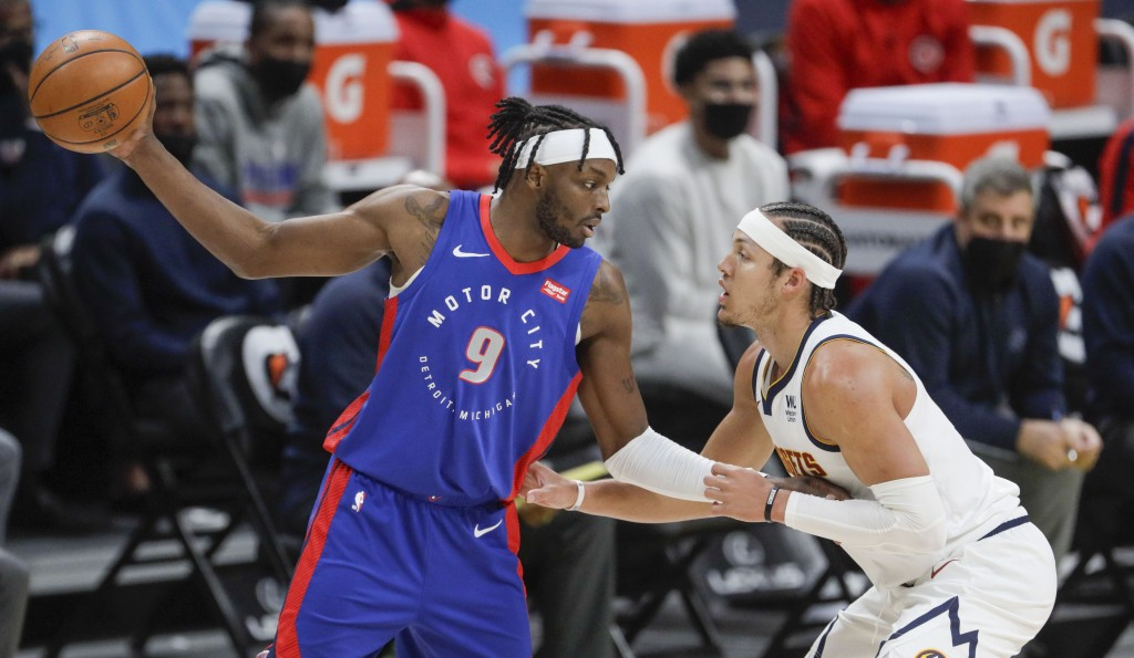 Detroit Pistons forward Jerami Grant (9) holds the ball away from Denver Nuggets forward Aaron Gordon (50) in the first quarter of an NBA basketball g...