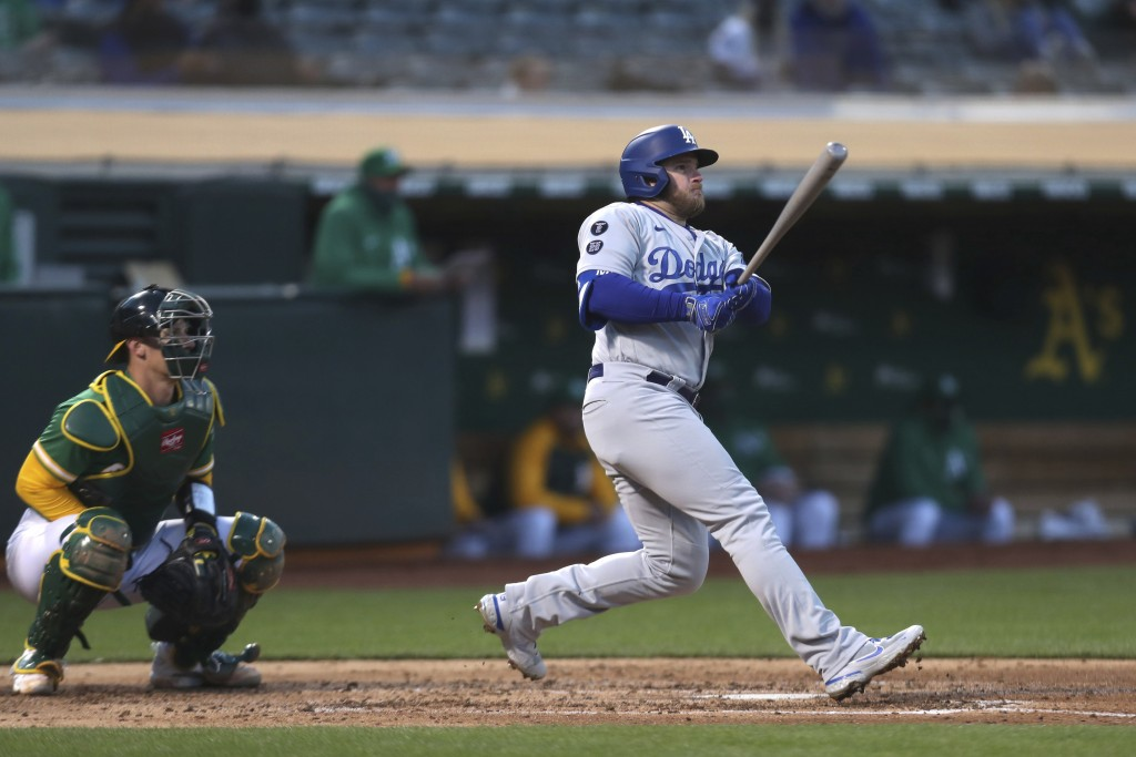 Los Angeles Dodgers' Max Muncy watches his two-run home run in front of the Oakland Athletics catcher Sean Murphy during the second inning of a baseba...
