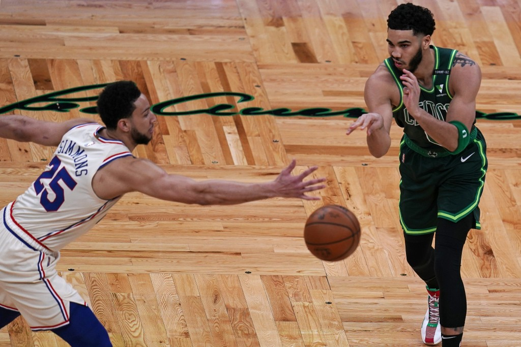Boston Celtics forward Jayson Tatum, right, passes the ball while pressured by Philadelphia 76ers guard Ben Simmons, left, during the first half of an...