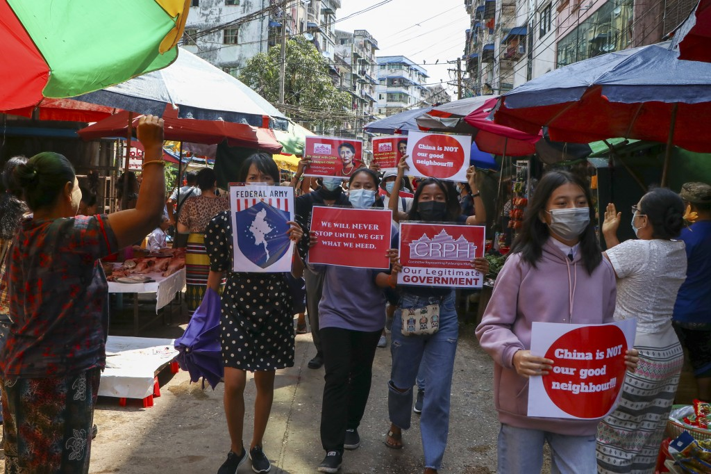 Anti-coup protesters hold slogans as they are greeted while marching along a market street in Yangon, Myanmar, Wednesday April 7, 2021. Threats of let...