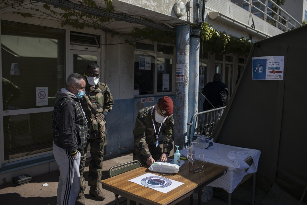 A French soldier receives people at a vaccination center set up at the Laveran Military Hospital in Marseille, southern France, Wednesday, April 7, 20...