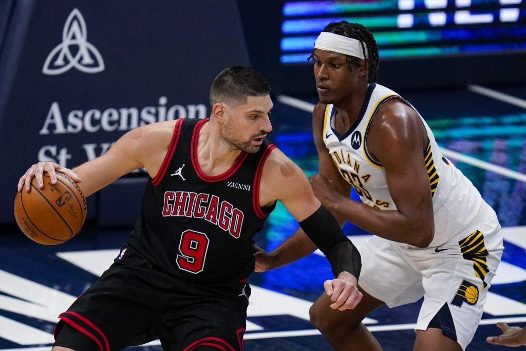 Chicago Bulls center Nikola Vucevic (9) drives on Indiana Pacers center Myles Turner (33) during the first half of an NBA basketball game in Indianapo...