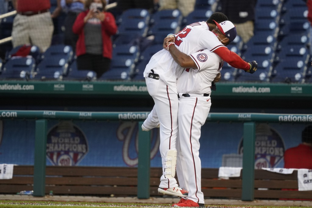 Washington Nationals' Juan Soto, left, celebrates with manager Dave Martinez after Soto hit a game-winning single in the ninth inning of an opening da...