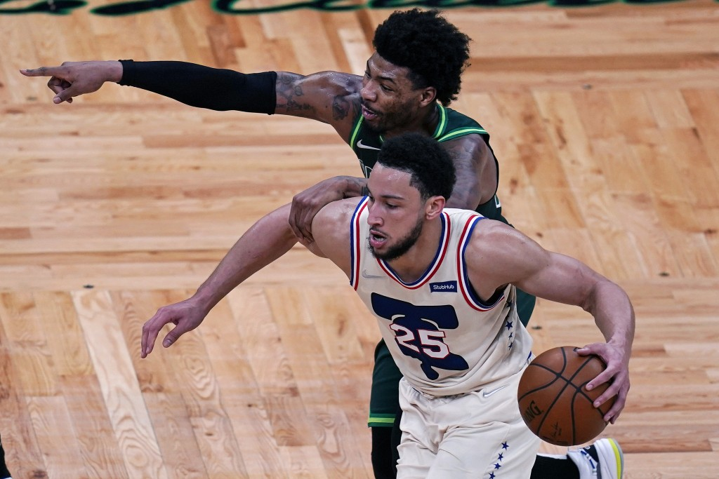 Boston Celtics guard Marcus Smart, left, points for help while trying to hold back Philadelphia 76ers guard Ben Simmons, right, during the second half...