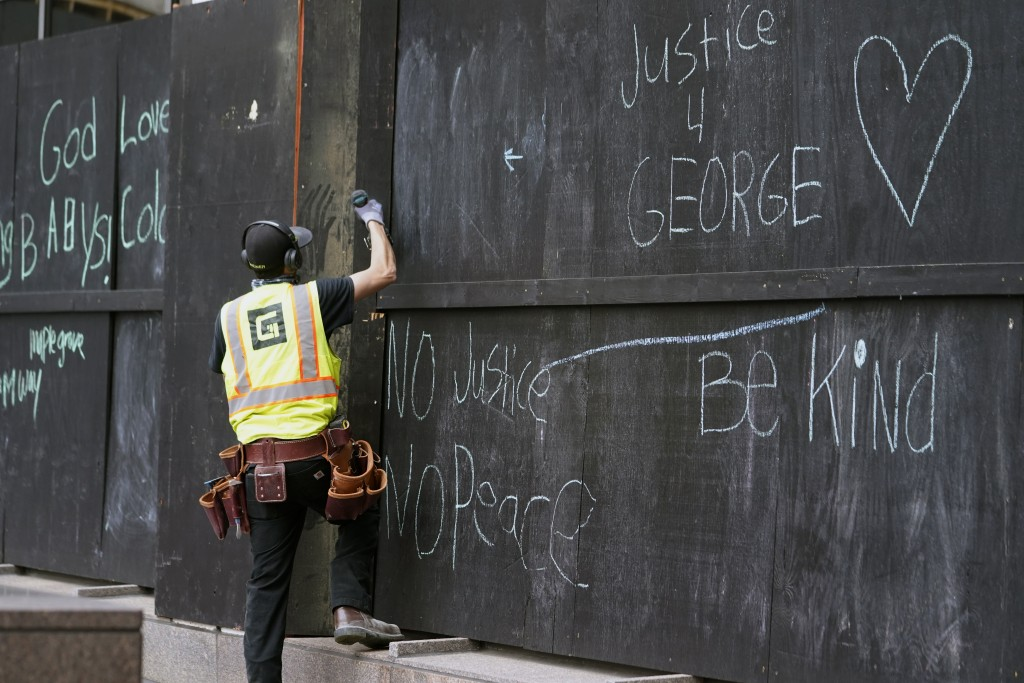 A worker installs another board on a boarded-up bank building across the street from the Hennepin County Government Center, Wednesday, April 7, 2021, ...