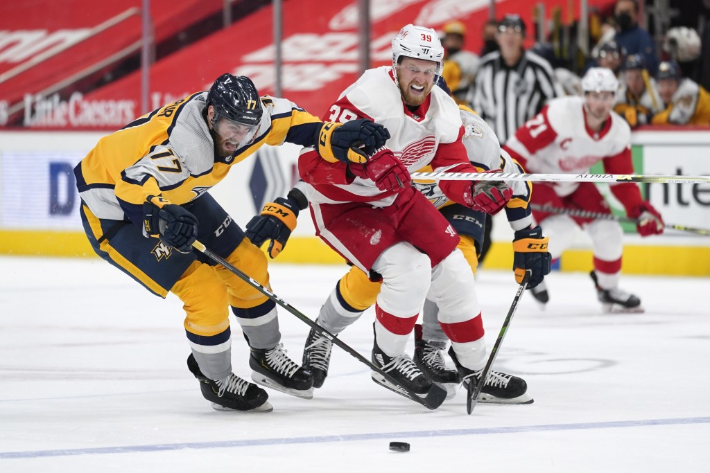 Nashville Predators defenseman Ben Harpur (17) and Detroit Red Wings right wing Anthony Mantha (39) chase a loose puck in the second period of an NHL ...