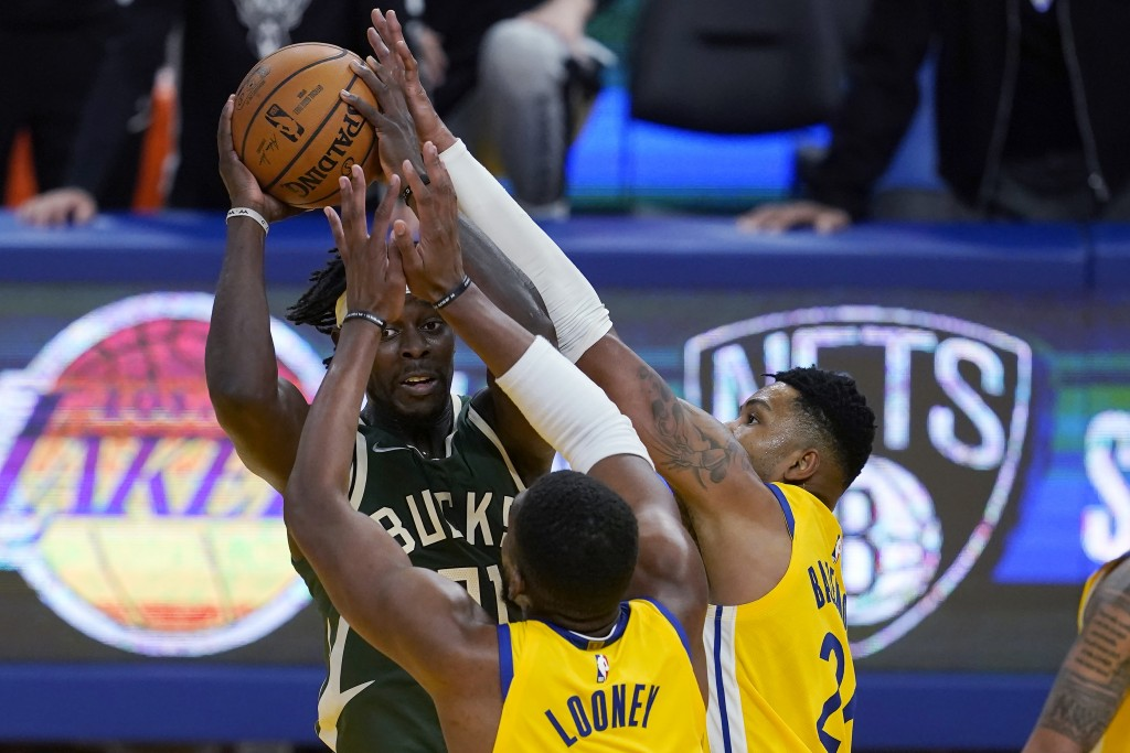 Milwaukee Bucks guard Jrue Holiday, rear, is defended by Golden State Warriors center Kevon Looney, bottom, and forward Kent Bazemore during the secon...
