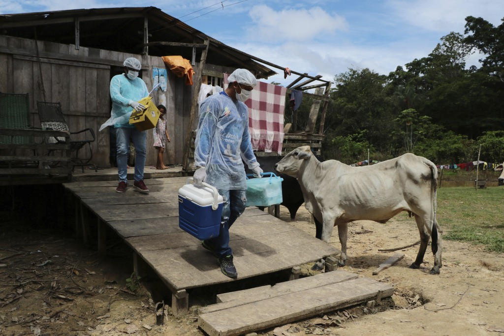 Health workers Diego Feitosa Ferreira, 28, right, and Clemilton Lopes de Oliveira, 41, leave a home after a resident denied to be vaccinated against t...