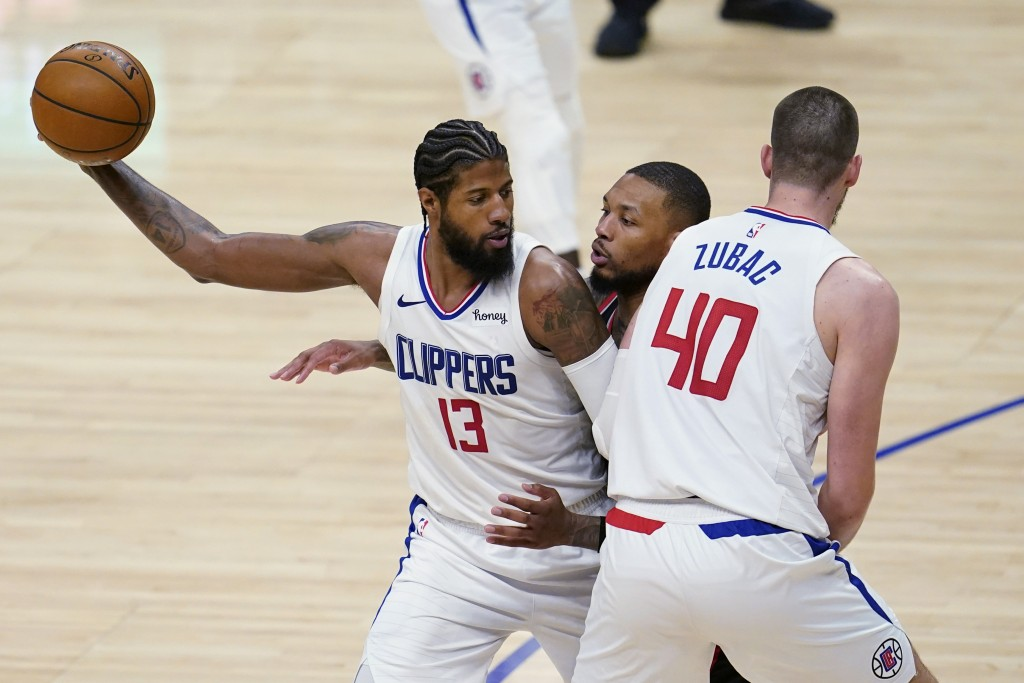 Los Angeles Clippers guard Paul George (13) holds the ball as Ivica Zubac (40) sets a screen on Portland Trail Blazers guard Damian Lillard, center, d...