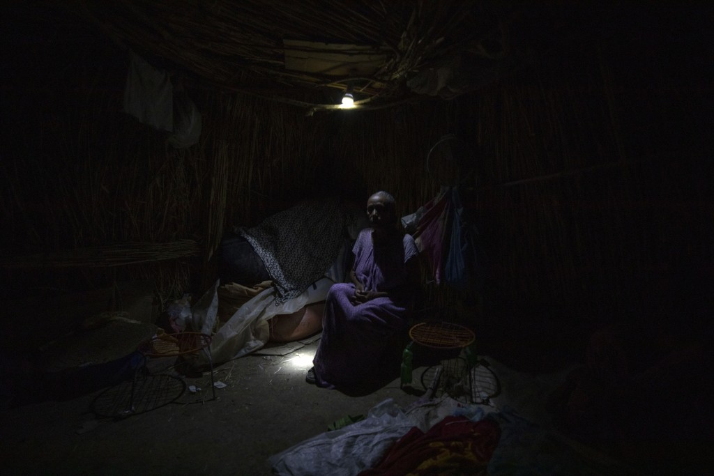 Tigrayan refugee Belaynesh Beyene, 58, who fled the conflict in the Ethiopia's Tigray, sits in her shelter in Hamdayet, eastern Sudan, near the border...