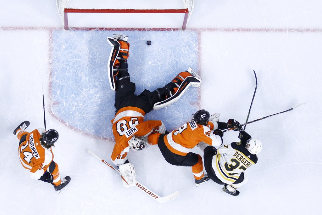 Boston Bruins' Patrice Bergeron, right, scores a goal past Philadelphia Flyers goaltender Carter Hart (79) as Ivan Provorov (9) and Sean Couturier (14...