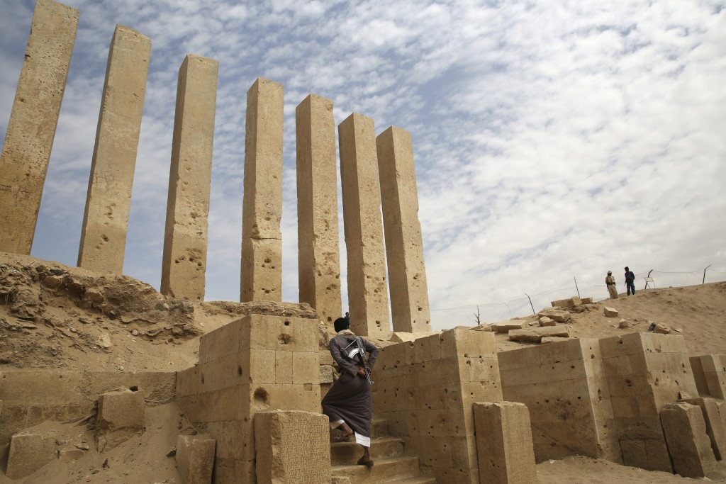 FILE - In this Feb. 3, 2018, file photo, a militiaman allied to Yemen's internationally recognized government walks through the Awwam Temple, also kno...