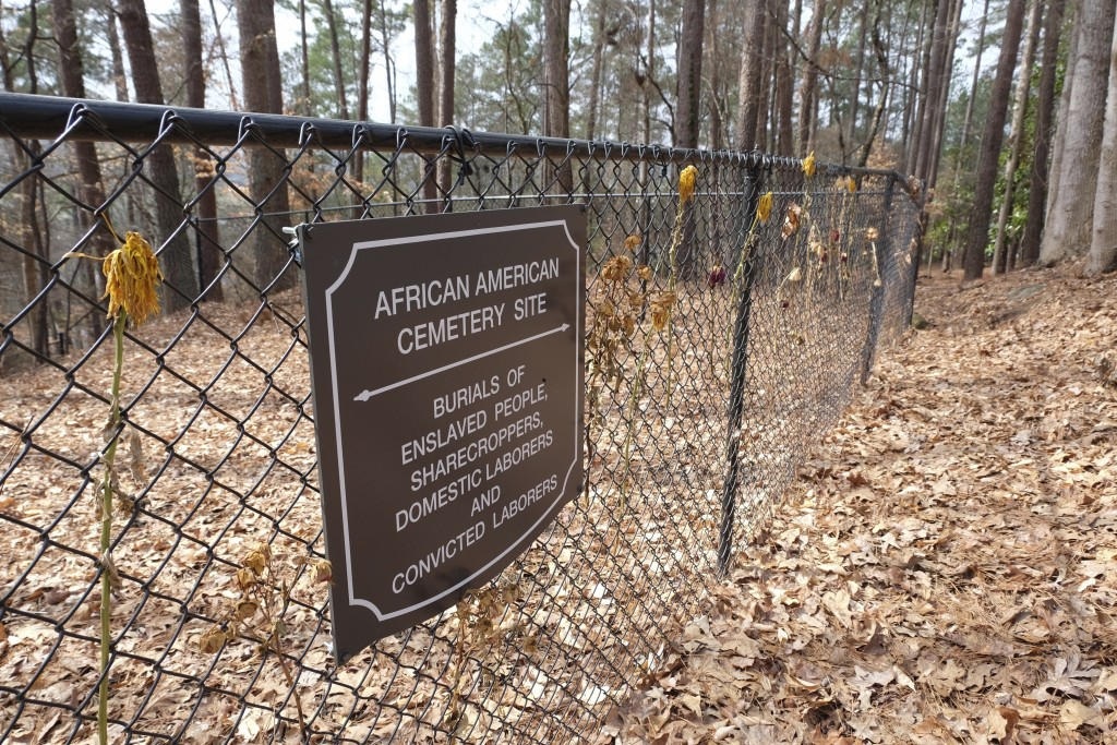 Flowers adorn a fence marking an African American cemetery site at Woodland Cemetery in Clemson, South Carolina on Sunday, Feb.  28, 2021.   Students ...