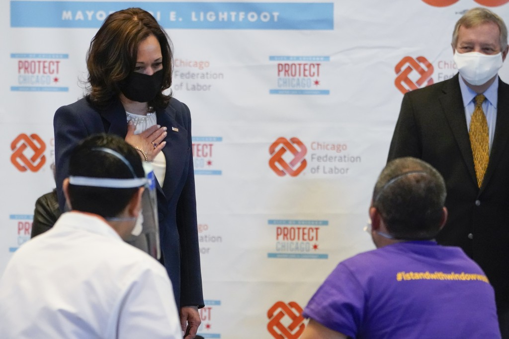 Vice President Kamala Harris talks with Lucio Polanco, a high-rise window washer, as he received the Johnson & Johnson COVID-19 vaccination from Osman...