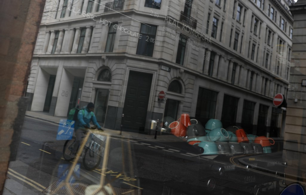 A Deliveroo worker cycles past a closed coffee shop near Guildhall in the City of London, Tuesday, April 6, 2021. When the pandemic struck, about 540,...