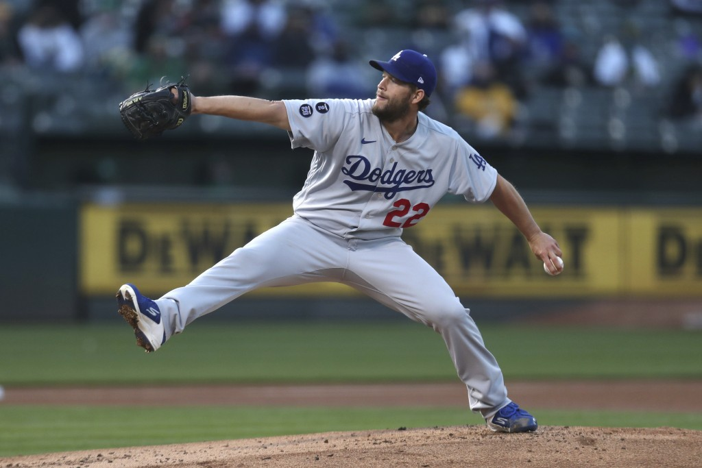 Los Angeles Dodgers pitcher Clayton Kershaw throws to an Oakland Athletics batter during the first inning of a baseball game in Oakland, Calif., Tuesd...