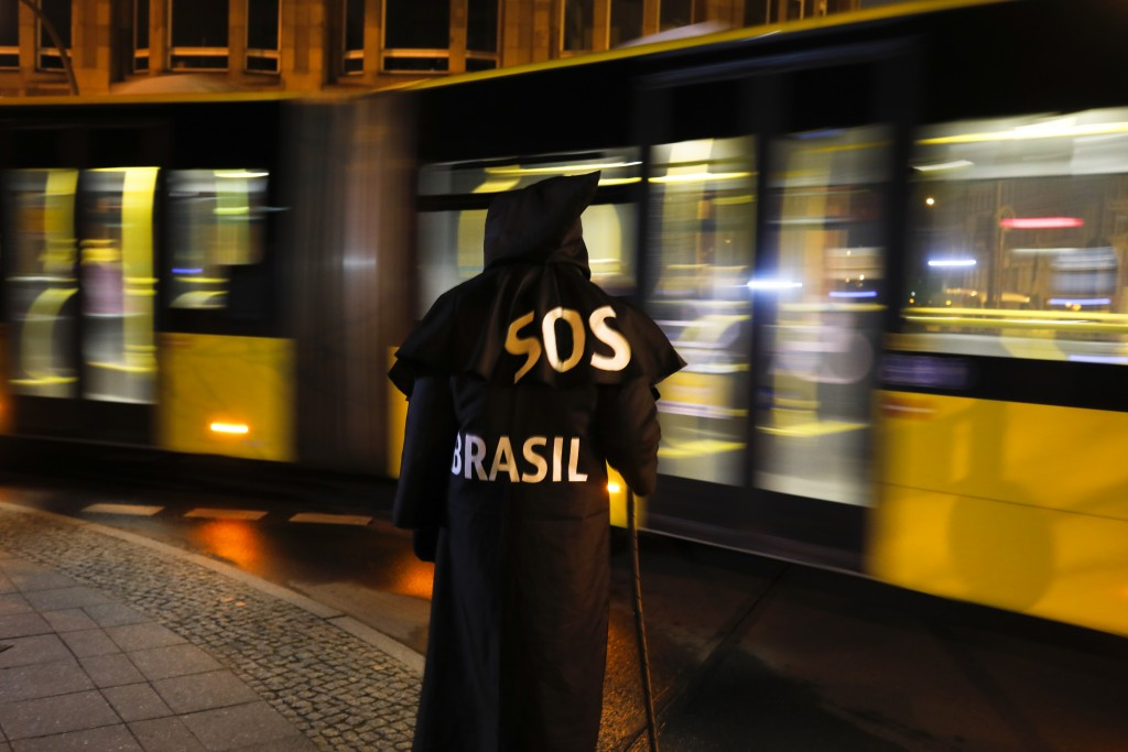 Brazilian activist and artist Rafael Puetter, dressed as the grim reaper, walks in a one-man protest through Berlin, Germany, early Wednesday, April 7...