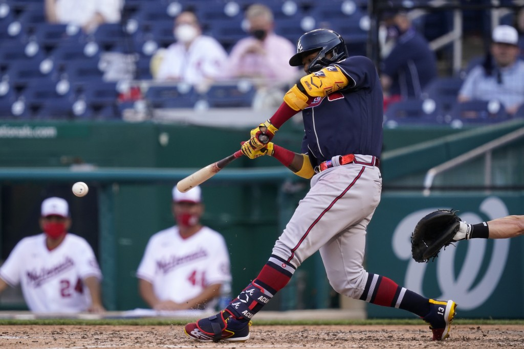 Atlanta Braves' Ronald Acuna Jr. hits a fielder's choice ground ball in the seventh inning of an opening day baseball game against the Washington Nati...
