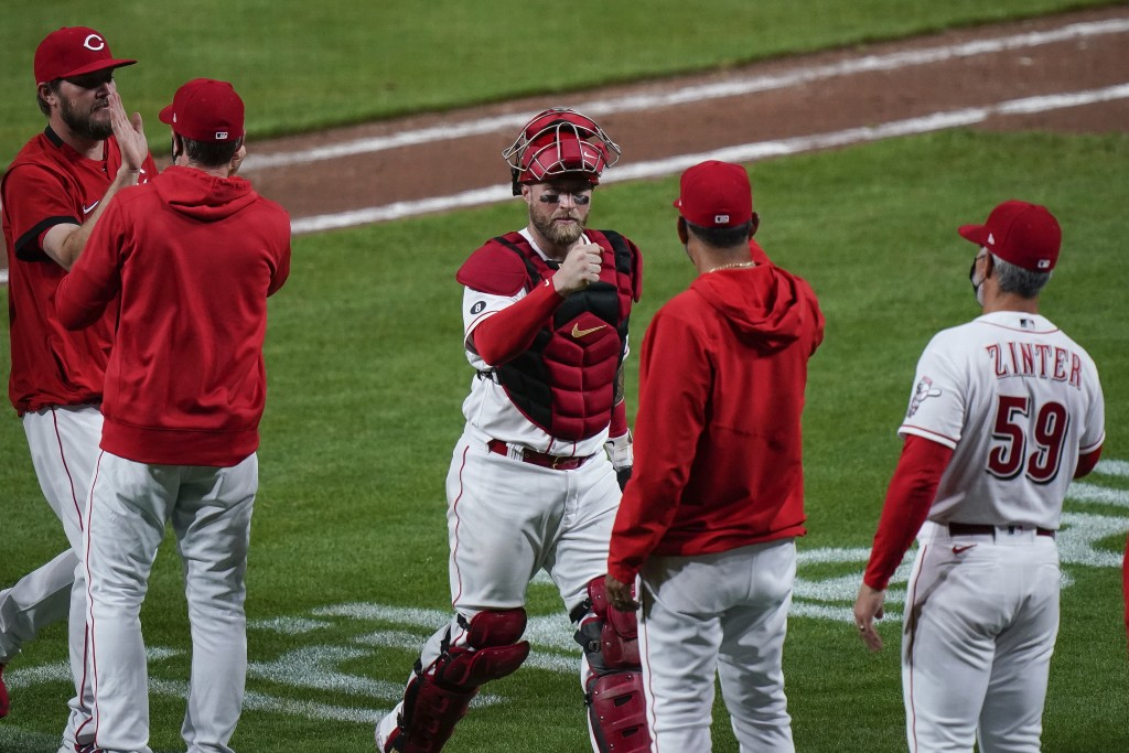 Cincinnati Reds' Cincinnati Reds' Tucker Barnhart, center,  celebrates with staff and teammates after defeating the Pittsburgh Pirates at Great Americ...