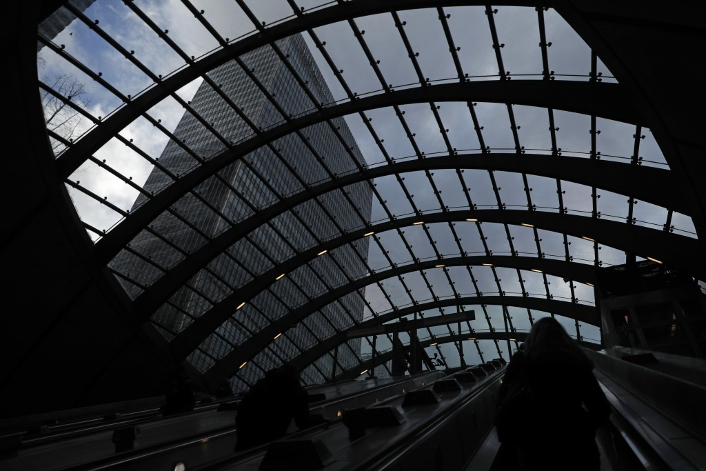 People use the escalator as they exit Canary Wharf underground station, with the JP Morgan building above them at left, in London, Thursday, March 25,...