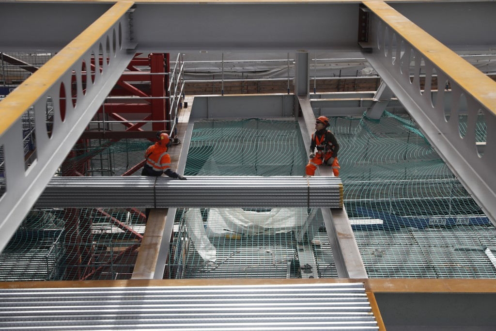Construction workers put down the steel flooring over the beams at the 8 Bishopsgate development in London, Thursday, April 1, 2021. When the pandemic...