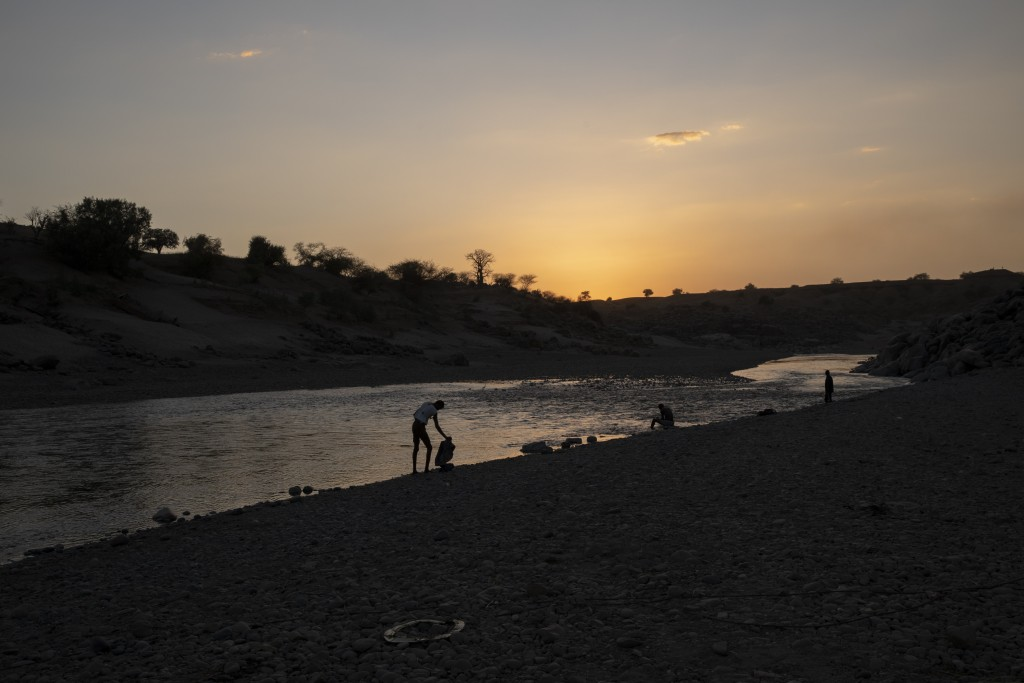 People stand on the banks of the Tekeze River, on the Sudan-Ethiopia border after Ethiopian forces blocked individuals from crossing into Sudan, near ...