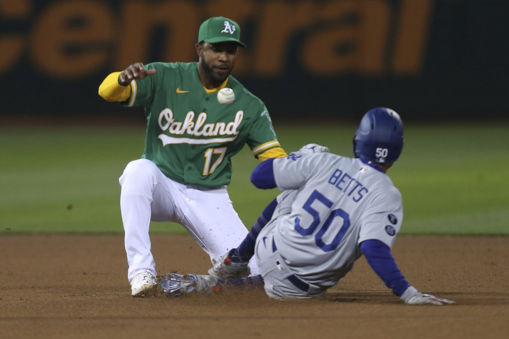 Los Angeles Dodgers' Mookie Betts, right, steals second base as Oakland Athletics shortstop Elvis Andrus tries to catch the throw during the fourth in...