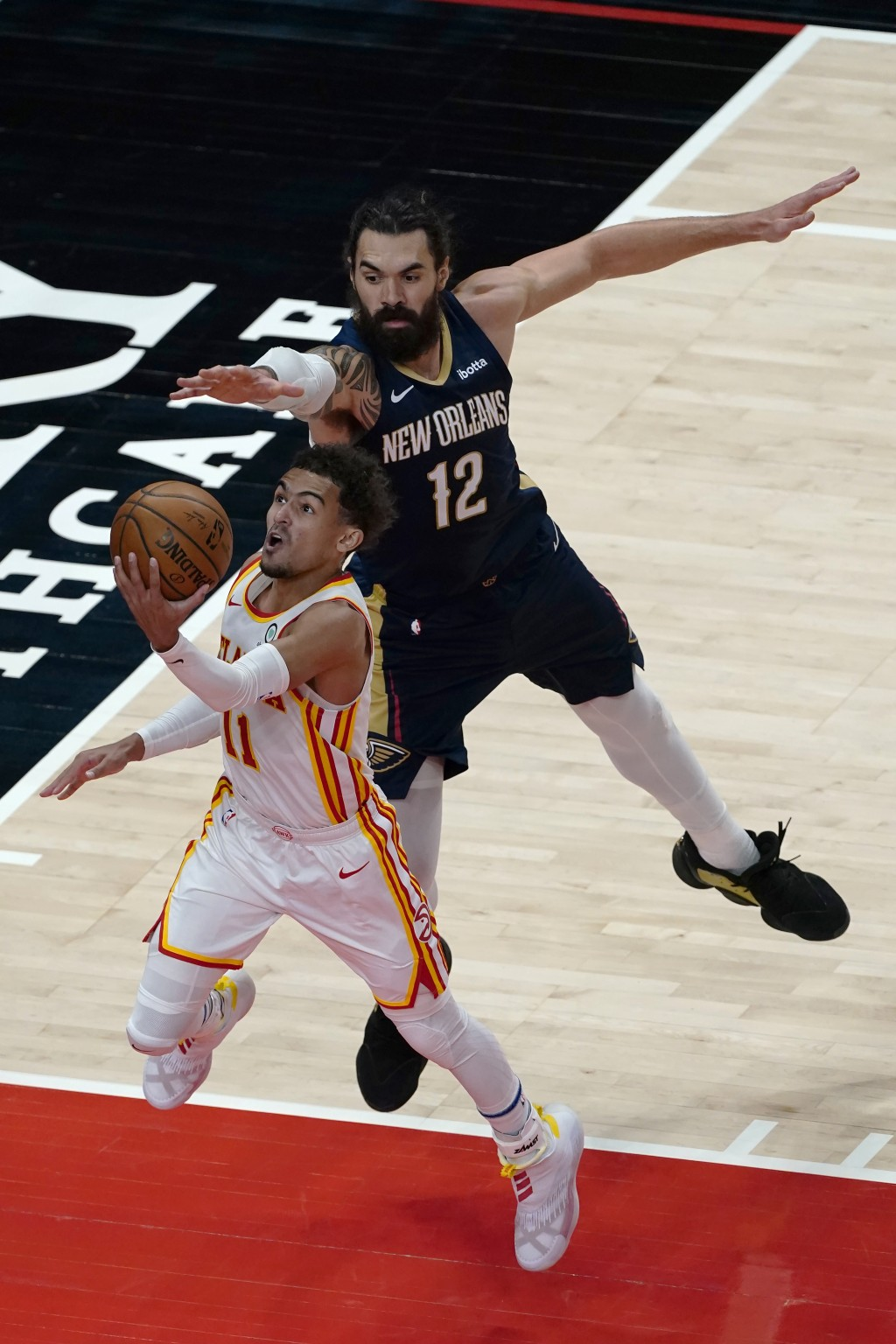 Atlanta Hawks guard Trae Young (11) goes to the basket as New Orleans Pelicans center Steven Adams (12) defends in the first half of an NBA basketball...