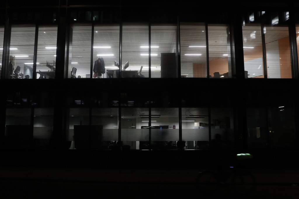 Lights shine from empty offices in the Barbican area of the City of London, Saturday, March 6, 2021. When the pandemic struck, about 540,000 workers v...