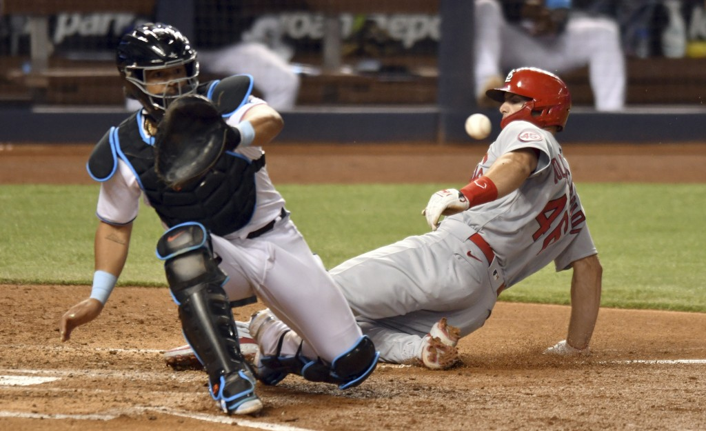 St. Louis Cardinals' Paul Goldschmidt scores as Miami Marlins catcher Jorge Alfaro waits for the throw during the sixth inning of a baseball game Tues...