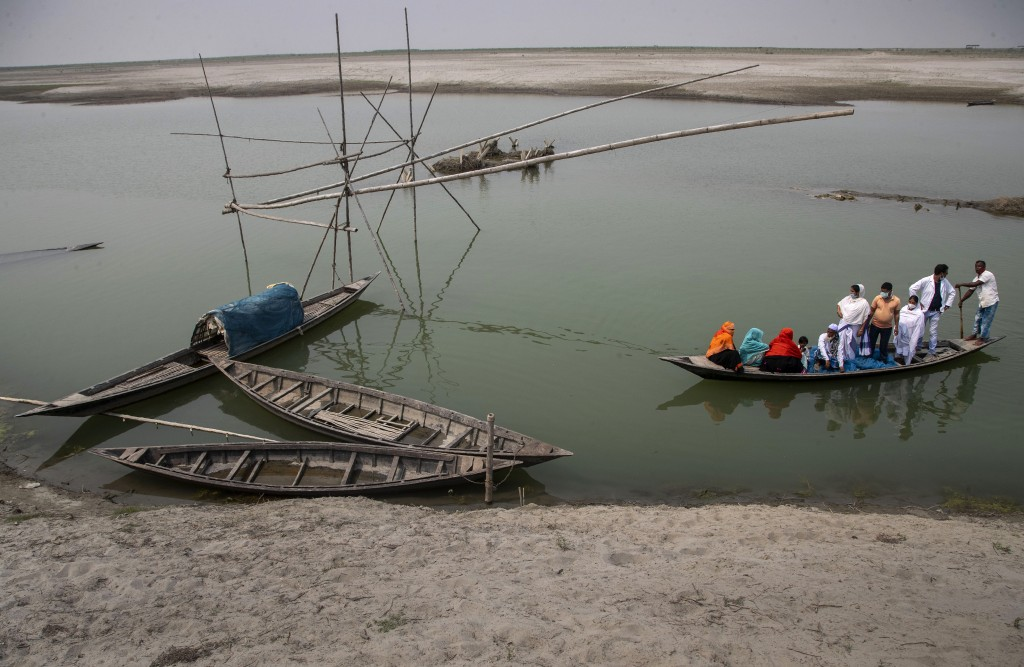 Health workers accompany elderly villagers in a boat as they cross the river Brahmaputra to reach a vaccination center for COVID-19 at Bahakajari vill...