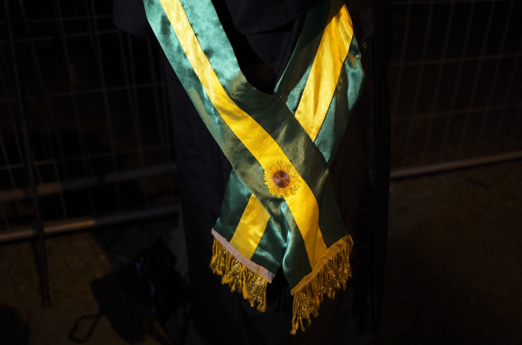 Brazilian activist and artist Rafael Puetter, is decorated with a sash in Brazilian colors prior to his one-man protest through Berlin, Germany, early...