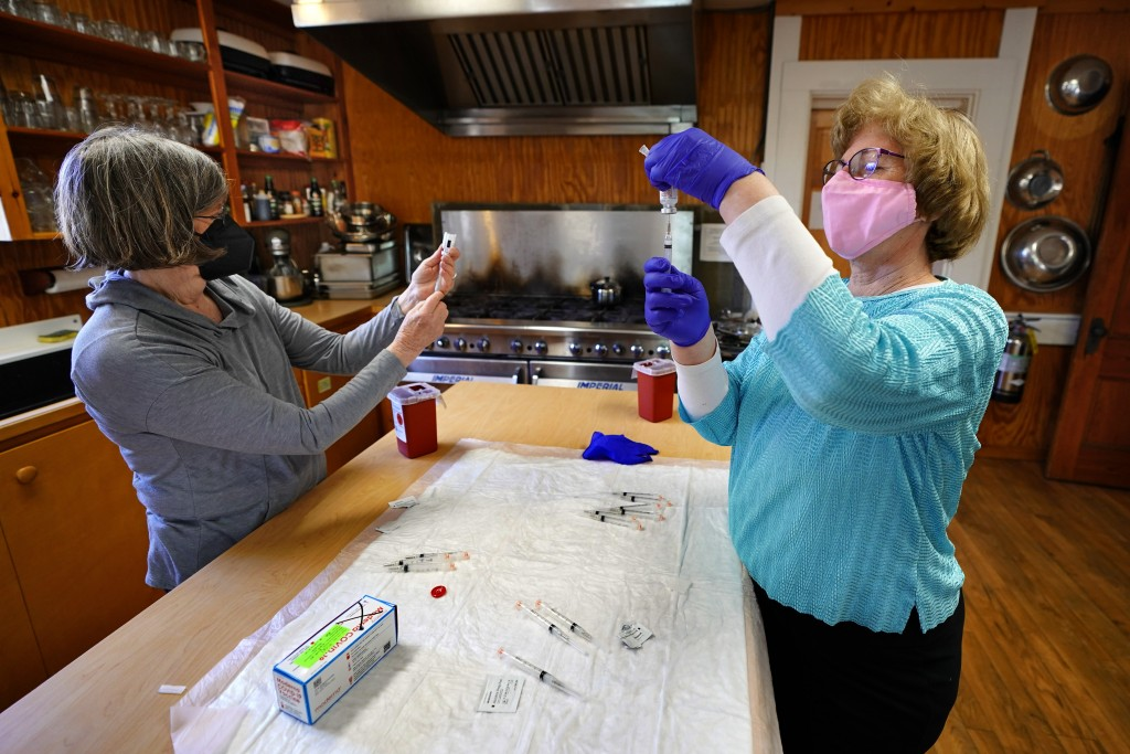 Nurses Sharon Daley, left, and Maureen Giffen fill syringes with the Moderna COVID-19 vaccine in a makeshift clinic in the kitchen of a community cent...