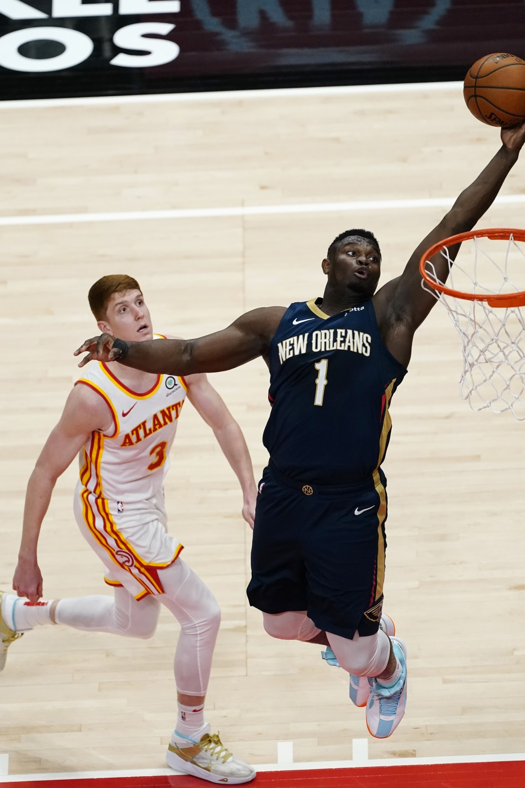 New Orleans Pelicans forward Zion Williamson (1) scores as Atlanta Hawks guard Kevin Huerter (3) defends in the first half of an NBA basketball game T...