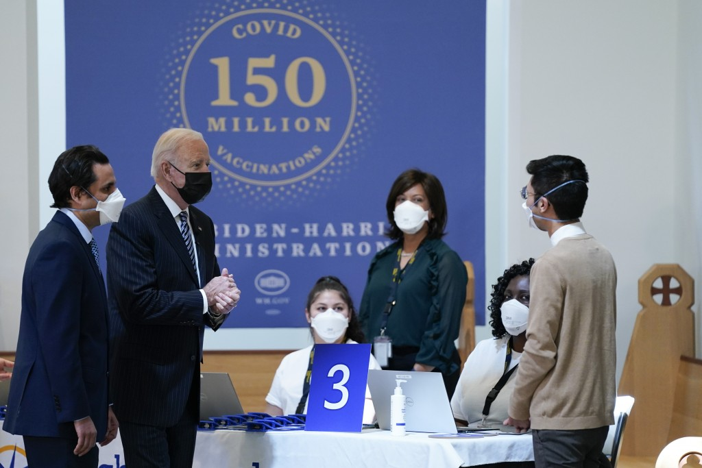 President Joe Biden speaks with health care workers as he visits a vaccination site at Virginia Theological Seminary, Tuesday, April 6, 2021, in Alexa...
