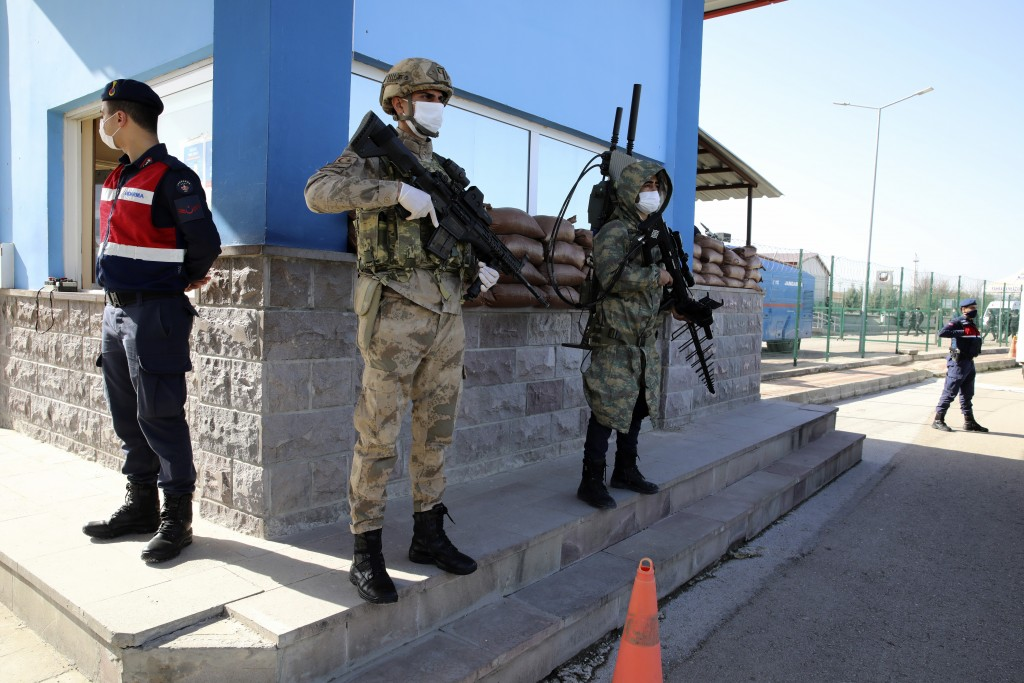 Soldiers stand in guard as people wait outside a courthouse before the trial of 497 defendants, in Sincan, outside the capital Ankara, Turkey, Wednesd...