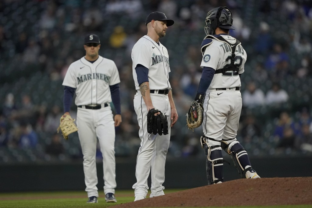 Seattle Mariners starting pitcher James Paxton, center, waits near the mound with catcher Luis Torrens after Paxton suffered an injury during the seco...