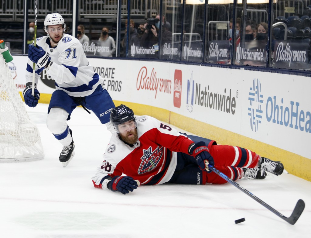 Columbus Blue Jackets defenseman David Savard, right, reaches for the puck in front of Tampa Bay Lightning forward Anthony Cirelli during the first pe...