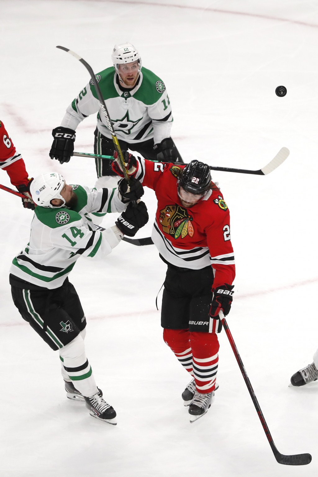 Dallas Stars left wing Jamie Benn (14) and Chicago Blackhawks center Ryan Carpenter (22) battle for the puck during the second period of an NHL hockey...