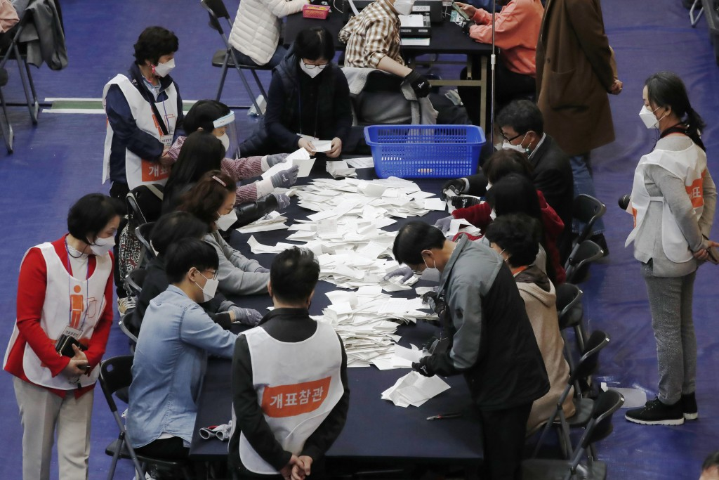 National Election Commission officials sort out ballots for counting at the Seoul mayoral by-election in Seoul, South Korea, Wednesday, April 7, 2021....
