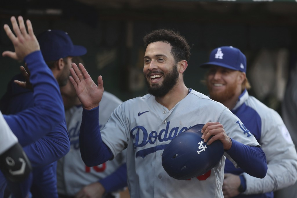 Los Angeles Dodgers' Edwin Rios is congratulated by teammates after hitting a home run against the Oakland Athletics during the third inning of a base...