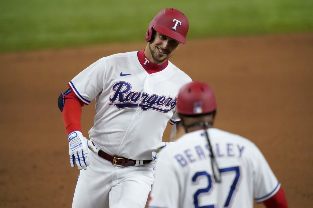 Texas Rangers' Nate Lowe, left, rounds third and is congratulated by third base coach Tony Beasley (27) after hitting a two-run home run against the T...