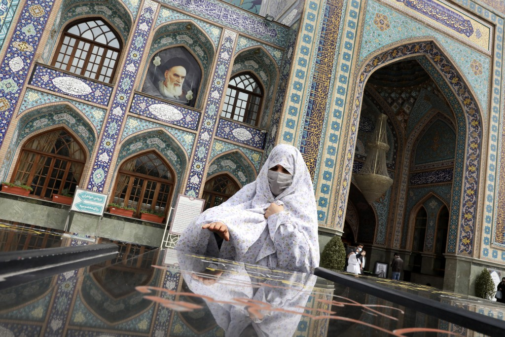 A woman prays at the grave of an unknown soldier who was killed during 1980-88 Iran-Iraq war, at the shrine of Saint Saleh in northern Tehran, Iran, T...