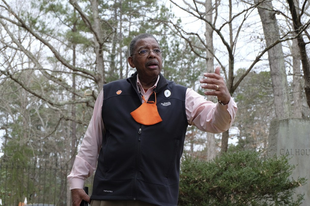 James E. Bostic, a former Clemson board member and the first African American to earn a doctorate at the school, talks to vistors at the Calhoun famil...